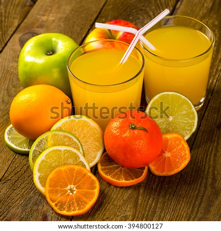 Fresh juice of ripe mandarins in a small glass with striped straw, selective focus