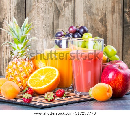 Fresh juice, orange and strawberry with fresh mix fruits on wooden table - stock photo