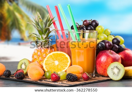 Fresh juice, orange with fresh mix fruits on wooden table and tropical beach background - stock photo