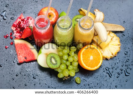 Fresh Juices Smoothie Red Green Yellow Tropical Fruits Water Melon Strawberry Apple Kiwi Orange Mango Banana Pine Apple Pomegranate Grape Selective focus Bottles multi-colour - stock photo