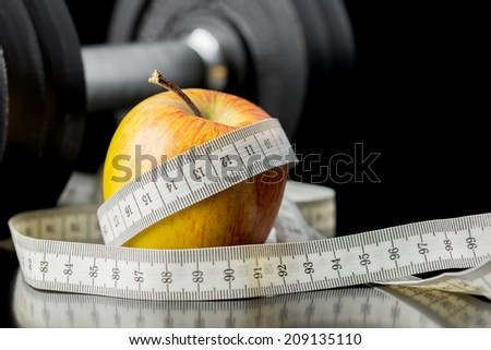 Fresh juicy apple wrapped in a tape measure with a gym weight visible behind conceptual of a healthy diet and nutrition , exercise , fitness and weight loss. - stock photo