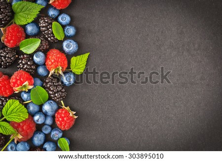Fresh juicy berries with green leaves on dark background - stock photo