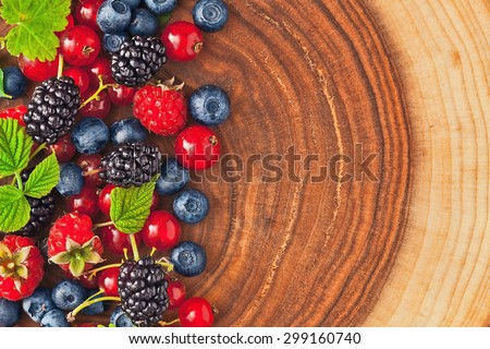 Fresh juicy berries with green leaves on wood texture - stock photo
