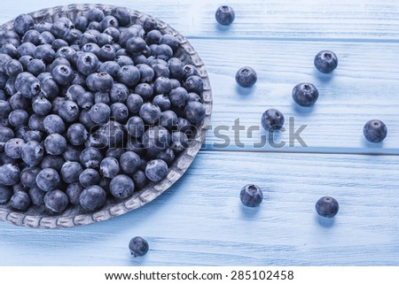 fresh, juicy blueberries on wooden, blue background