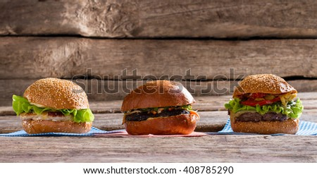Fresh juicy burgers. Burgers laying on wooden table. Tasty breakfast that brings energy. Usual working day snack. - stock photo