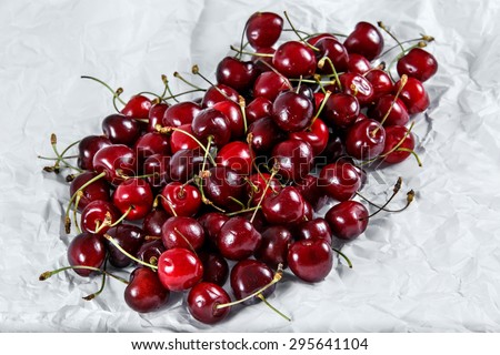 Fresh Juicy Cherries. scattered  on crumpled paper - stock photo