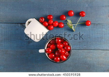 Fresh juicy cherry in a cup on a wooden background. Rustic food style, dark photo. Top view, flat style,  - stock photo