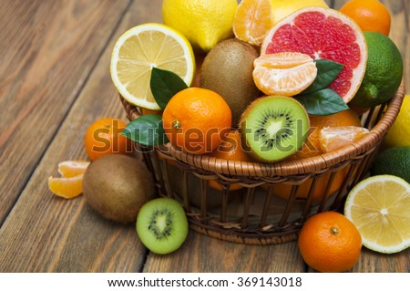 Fresh juicy citrus fruits in a basket on a wooden background - stock photo