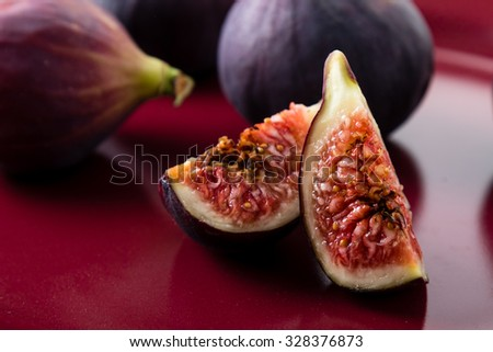 fresh juicy cut figs on a red color plate