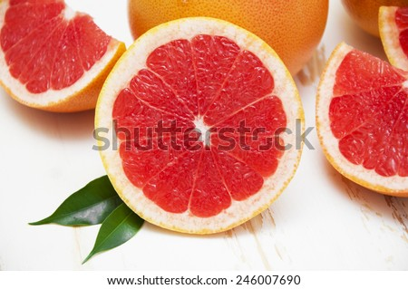 Fresh juicy grapefruits with green leafs on wooden background - stock photo