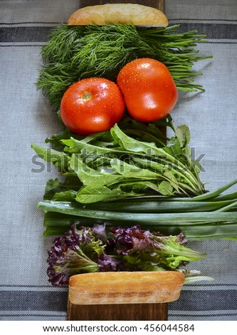 Fresh juicy greens and vegetables with bread. Green onions, tomatoes, arugula, lettuce, dill for a sandwich. - stock photo
