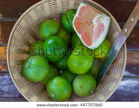 Fresh juicy lemons and a part of grapefruit in basket on wooden table - stock photo