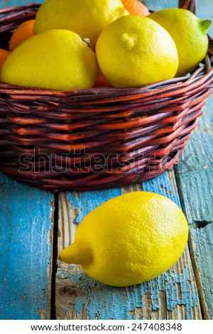Fresh juicy lemons in a basket on a rustic blue background - stock photo