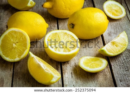 Fresh juicy lemons on a rustic wooden background - stock photo