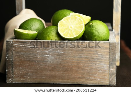 Fresh juicy limes in wooden crate, on dark background - stock photo