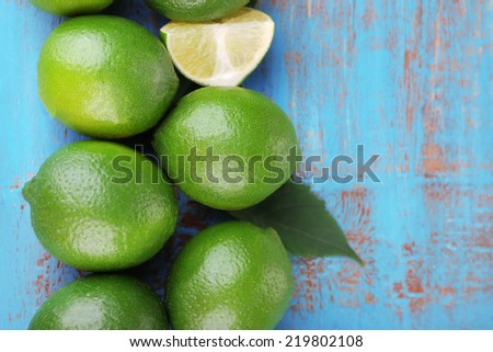 Fresh juicy limes on old wooden table - stock photo