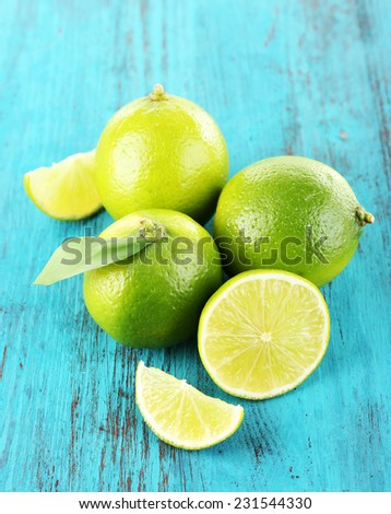 Fresh juicy limes on wooden background - stock photo
