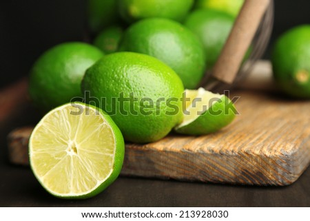 Fresh juicy limes on wooden table, on dark background - stock photo
