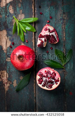 Fresh juicy pomegranate - whole and cut, with leaves on a wooden vintage background, top view - stock photo