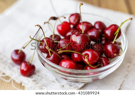 Fresh juicy sweet cherries in glass bowl. Rustic background with homespun napkin. - stock photo