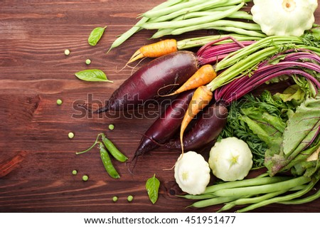Fresh juicy vegetables on brown wooden board. Young carrots and beets with leaves. Vegan concept