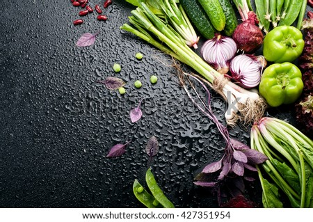 Fresh juicy vegetables such as  basil,  purple onion, young peas, peppers, green garlic and spinach on black background. Vegan concept.  Place for writing text. Vegetable background - stock photo