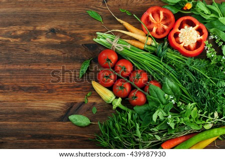 Fresh juicy vegetables such as red peppers, tomatoes, baby carrots, greens and herbs on a brown wooden background. Vegetable background. Vegan concept - stock photo