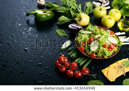 Fresh juicy vegetarian salad with lettuce, cucumbers and cherry tomatoes on a black background. Near a variety of fruits and vegetables, such as green onions, spinach, lemon and apple. Vegan menu. - stock photo