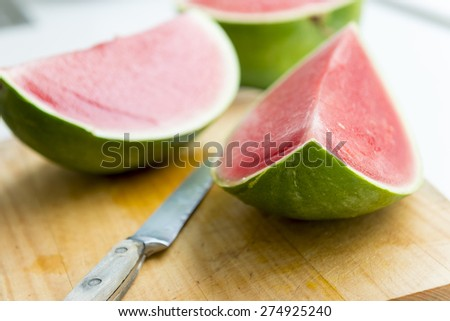 Fresh juicy watermelon slices on wooden board in shallow focus - stock photo