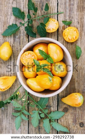 Fresh juicy yellow tomatoes on a wooden board - stock photo