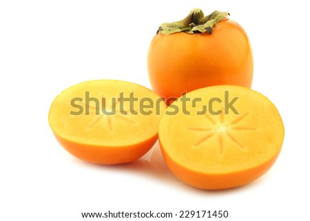fresh kaki fruit and two halves on a white background - stock photo