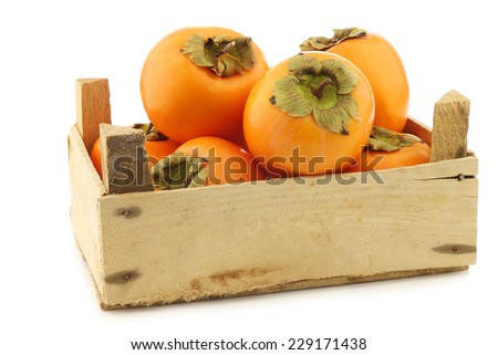 fresh kaki fruit in a wooden crate on a white background - stock photo