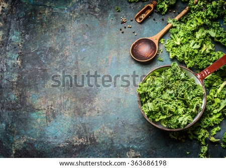 Fresh kale in cooking pot with wooden spoon on  rustic background, top view, border. Healthy food or diet nutrition concept.  - stock photo