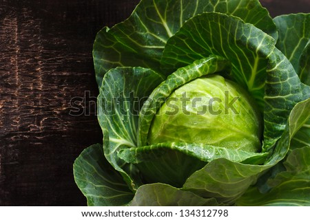 Fresh kitchen garden cabbage with water drops on a wooden background. - stock photo