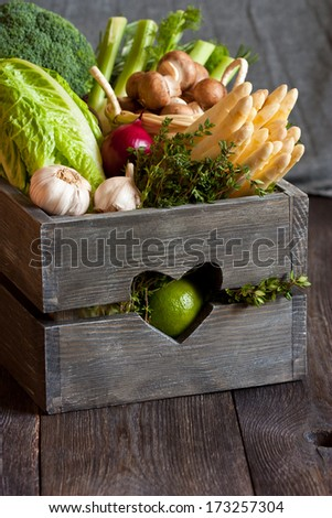 Fresh kitchen garden vegetables in an old wooden box. - stock photo