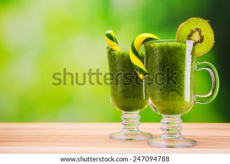 Fresh kiwi cocktails on wooden table - stock photo
