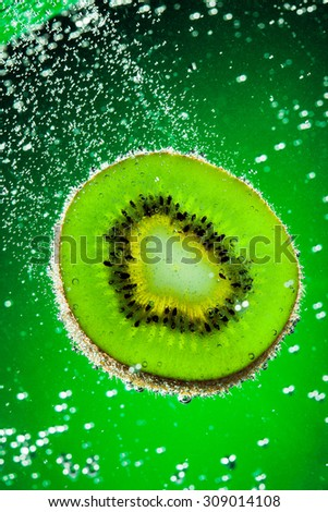 Fresh kiwi falls in water on a green background - stock photo
