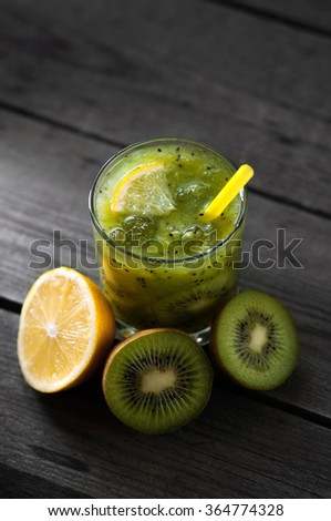 Fresh kiwi fruit and orange, healthy drink on wooden table.