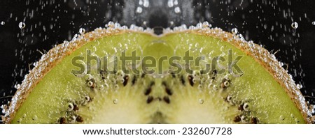 fresh kiwi is in water on a black background - stock photo