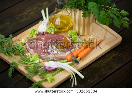 Fresh lamb steak with garlic, herbs, olive oil and garden vegetables