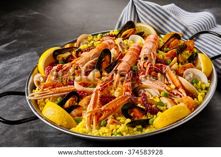 Fresh langoustines in a seafood Valencia paella with clams, mussels and octopus on a bed of saffron rice garnished with lemon slices in a gourmet presentation - stock photo