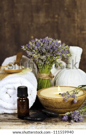 Fresh  lavender flowers, zen stones, essential oil, candle, Herbal massage balls  and towel over wooden surface - stock photo