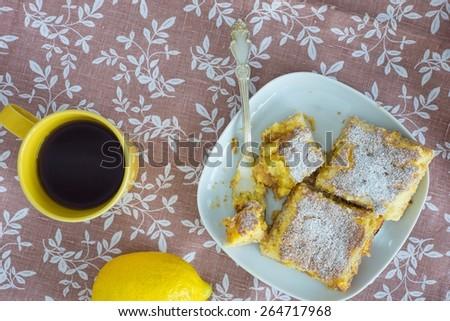 Fresh lemon cake on a plate, cup with tea and lemon fruit on lin - stock photo