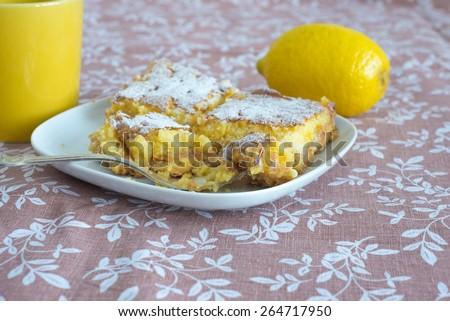 Fresh lemon cake, yellow cup and lemon fruit on patterned fabric - stock photo