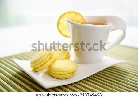 Fresh lemon macarons with tea - stock photo