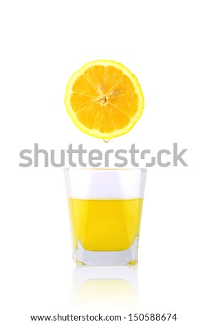 Fresh lemon over glass of lemon juice