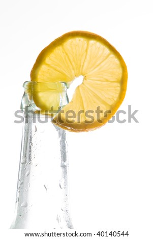 Fresh lemon slice decorates a bottle with a cold drink. Isolated on white with plenty of copy space. - stock photo