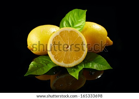 fresh lemon with drops of water on black background - stock photo