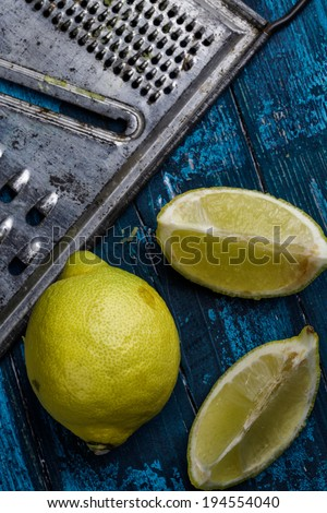Fresh Lemon with metal grater on blue board - stock photo