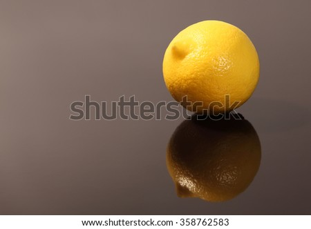 Fresh lemon with reflection in dark gray surface